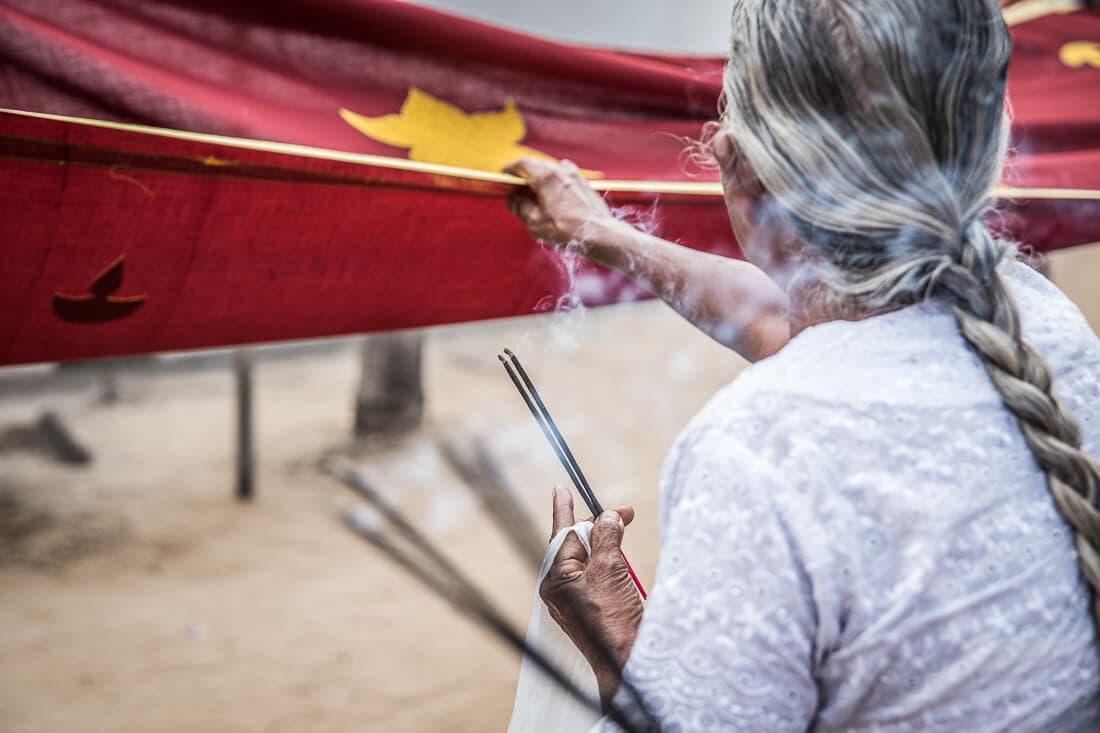 Alte Frau mit mit langem Zopf und Räucherstäbchen